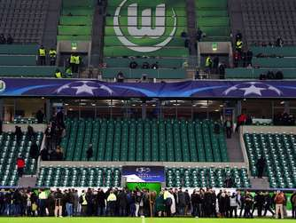People wait on the pitch after the end of the game during the UEFA Champions League Group B second-leg football match VfL Wolfsburg vs Manchester United in Wolfsburg, central Germany, on December 8, 2015. AFP PHOTO / JOHN MACDOUGALL