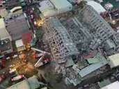 "This video frame grab taken and provided by CTI TV on February 6, 2016 shows an aerial view of the site of a collapsed building in the southern Taiwanese city of Tainan following a strong 6.4-magnitude earthquake that struck Taiwan early on February 6, 2016. A powerful earthquake in Taiwan felled a 16-storey apartment complex full of families who had gathered for Lunar New Year celebrations in the early hours of February 6, with at least seven dead and more than 30 feared trapped. AFP PHOTO / CTI TV ---EDITORS NOTE--- RESTRICTED TO EDITORIAL USE - MANDATORY CREDIT ""AFP PHOTO / CTI TV"" - NO MARKETING NO ADVERTISING CAMPAIGNS - DISTRIBUTED AS A SERVICE TO CLIENTS"